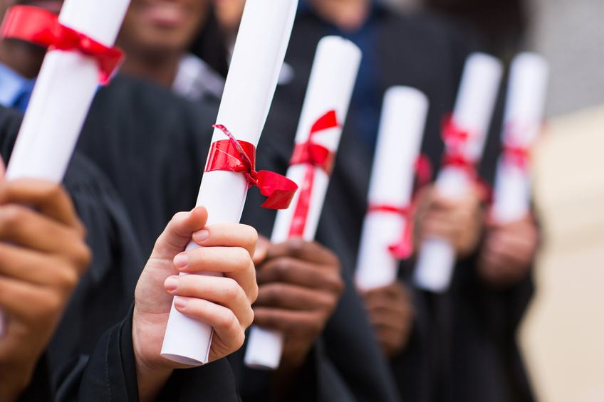 Multiracial graduates holding diplomas as they graduate from college
