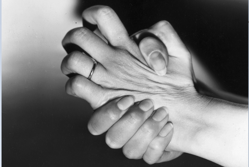 A woman nervously wrings her hands