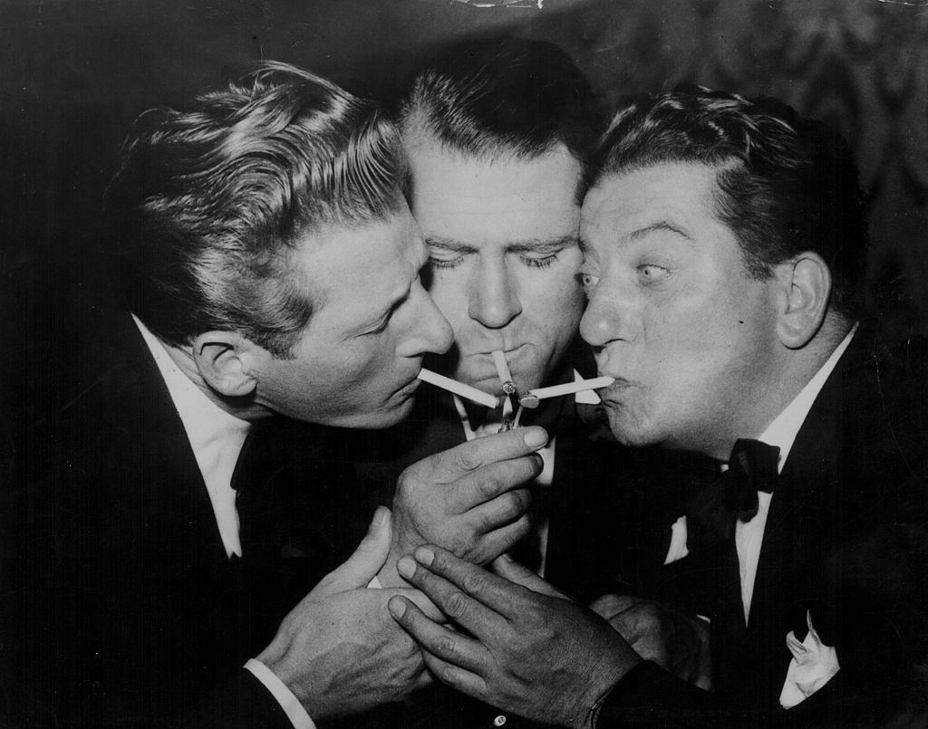 Actors Danny Kaye, Laurence Olivier, and Sid Field lighting their cigarettes from one flame