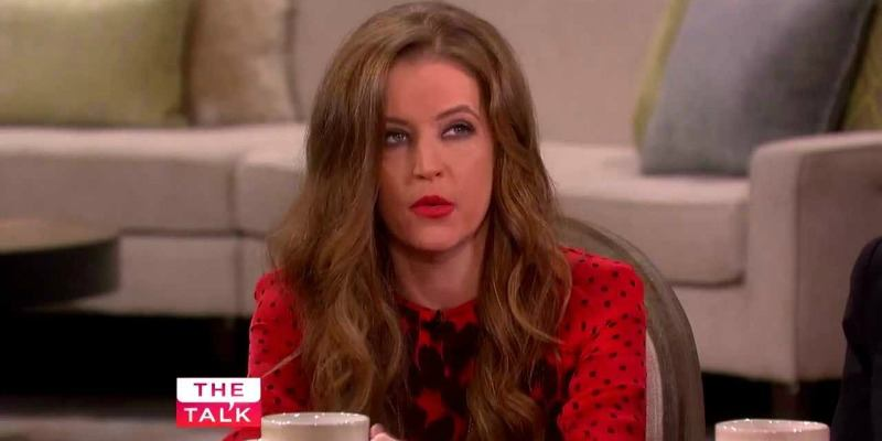 Lisa Marie Presley is talking and holding a coffee mug on The Talk.