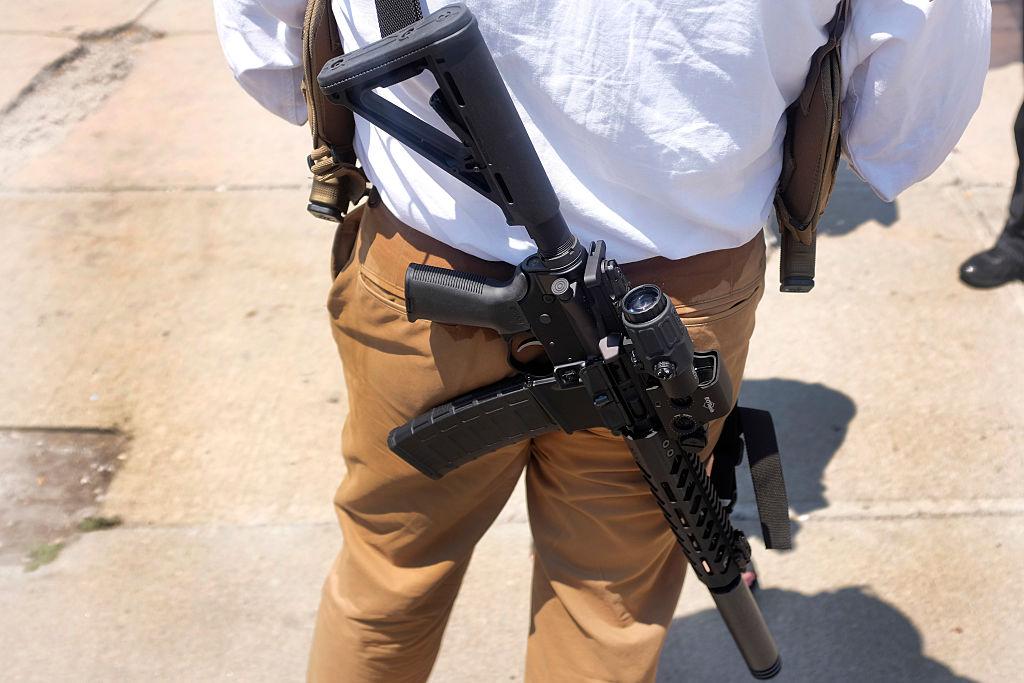 man carrying guns
