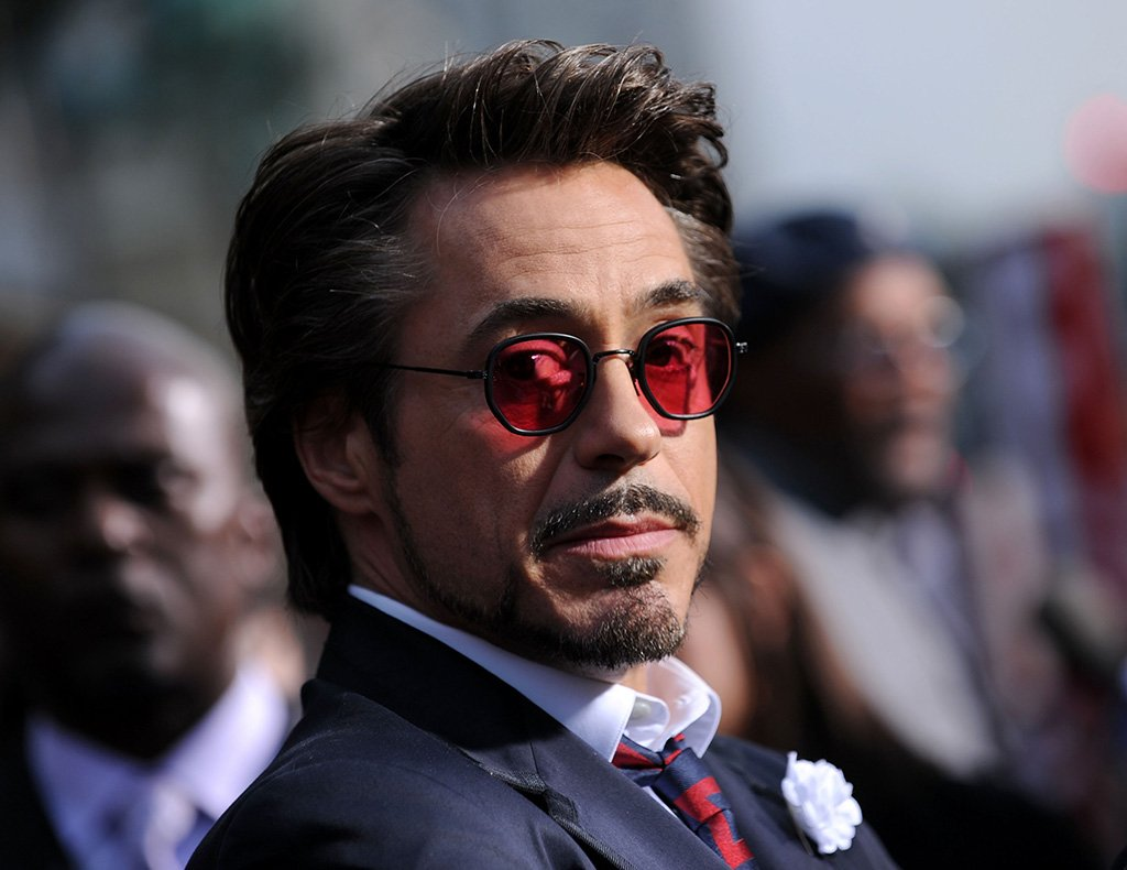 Rober Downey Jr. in red sunglasses, and a dapper blue suit with a red tie