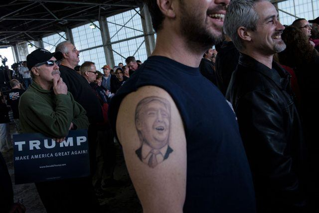 Man at an event for Donald Trump with his face tattooed on his arm