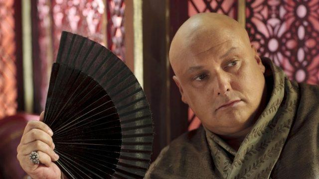 Varys holding a black fan and wearing a green robe.