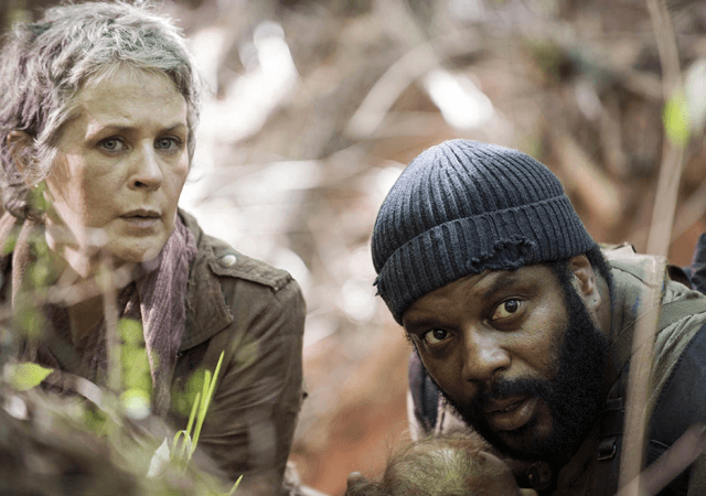 Carol and Tyreese hiding behind Tre branches.