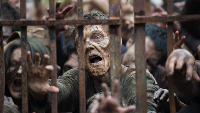 A group of zombies reach through a fence in a scene from 'The Walking Dead.'