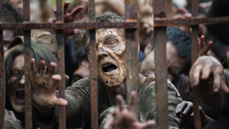 A group of zombies pile up against a fence in AMC's The Walking Dead