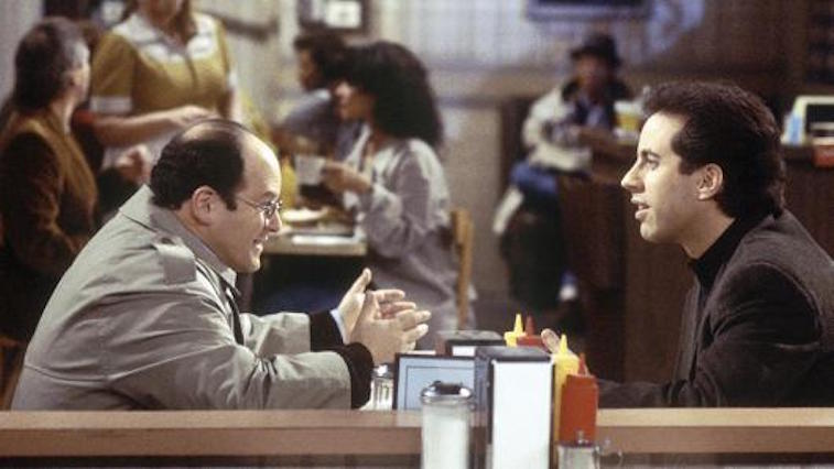 Jason Alexander as George Costanza and Jerry Seinfeld sitting in a booth in a diner on Seinfeld