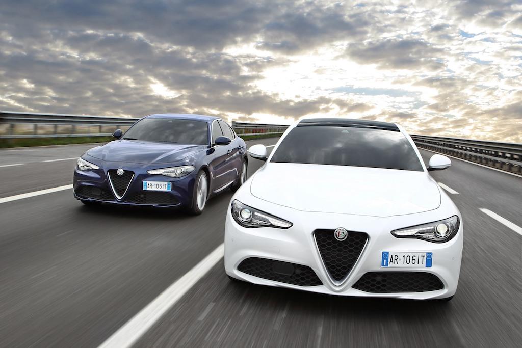 Two 2017 Alfa Romeo Giulias racing down the highway.