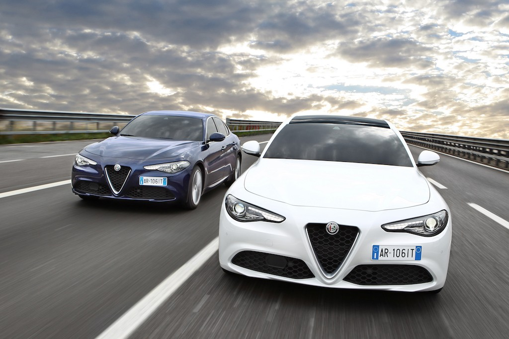 Two 2017 Alfa Romeo Giulias racing down the highway.