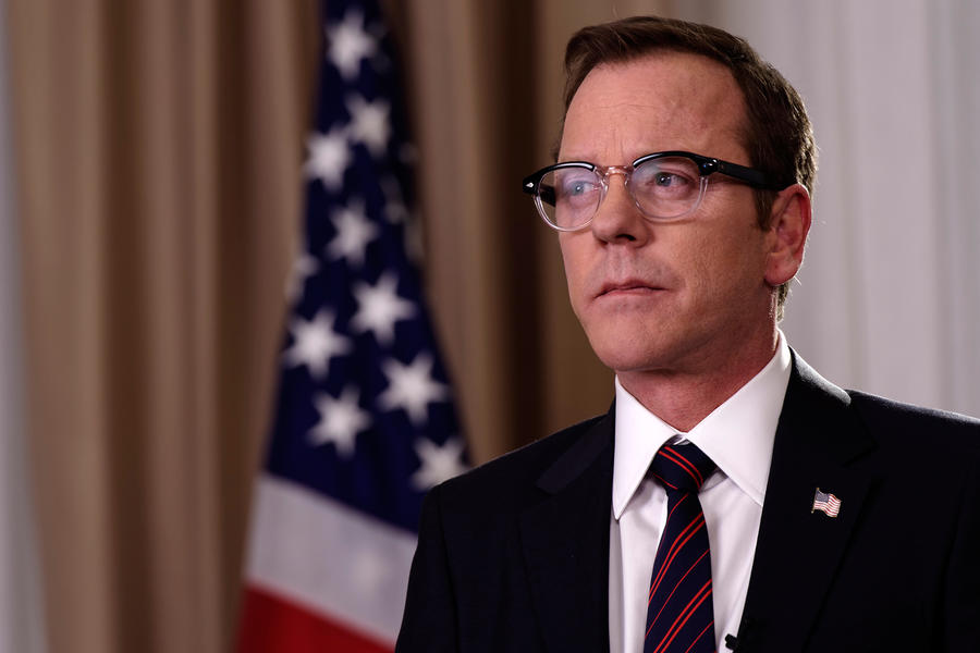Kiefer Sutherland stands in front of an American flag in Designated Survivor