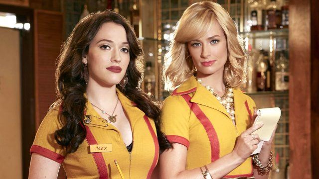 Kat Dennings and Beth Behrs in yellow and red waitress uniforms holding pencils and notepads in 2 Broke Girls