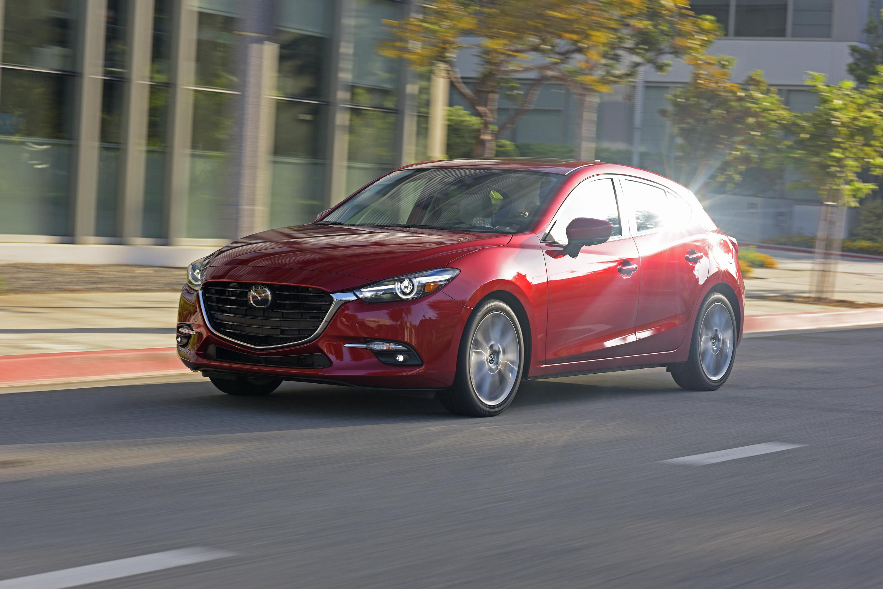 View of red 2017 Mazda3 in motion on city street