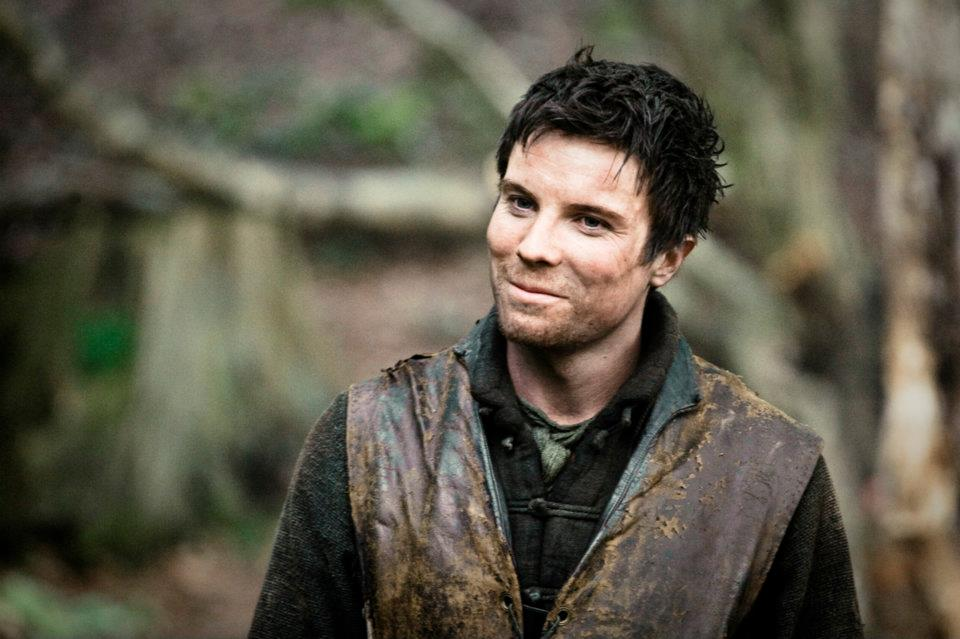 Gendry, wearing a brown leather vest, and smiling