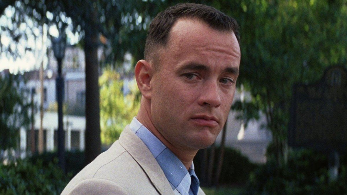 Tom Hanks as Forrest Gump, in a white suit looking off over his right shoulder