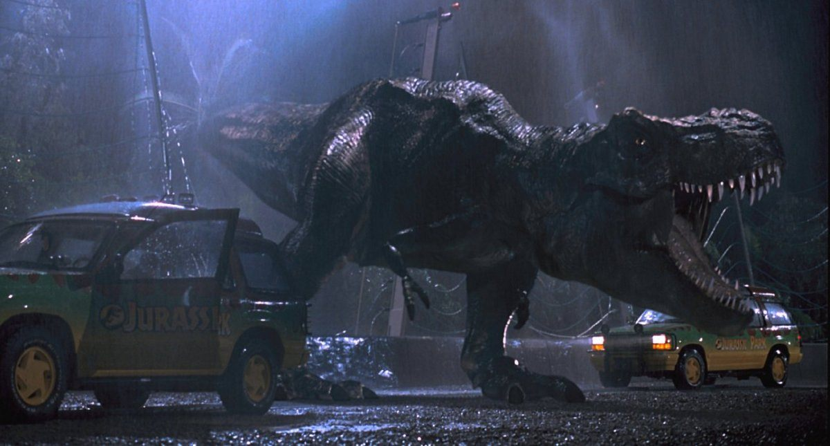 A T-Rex is roaring while standing next to two cars.