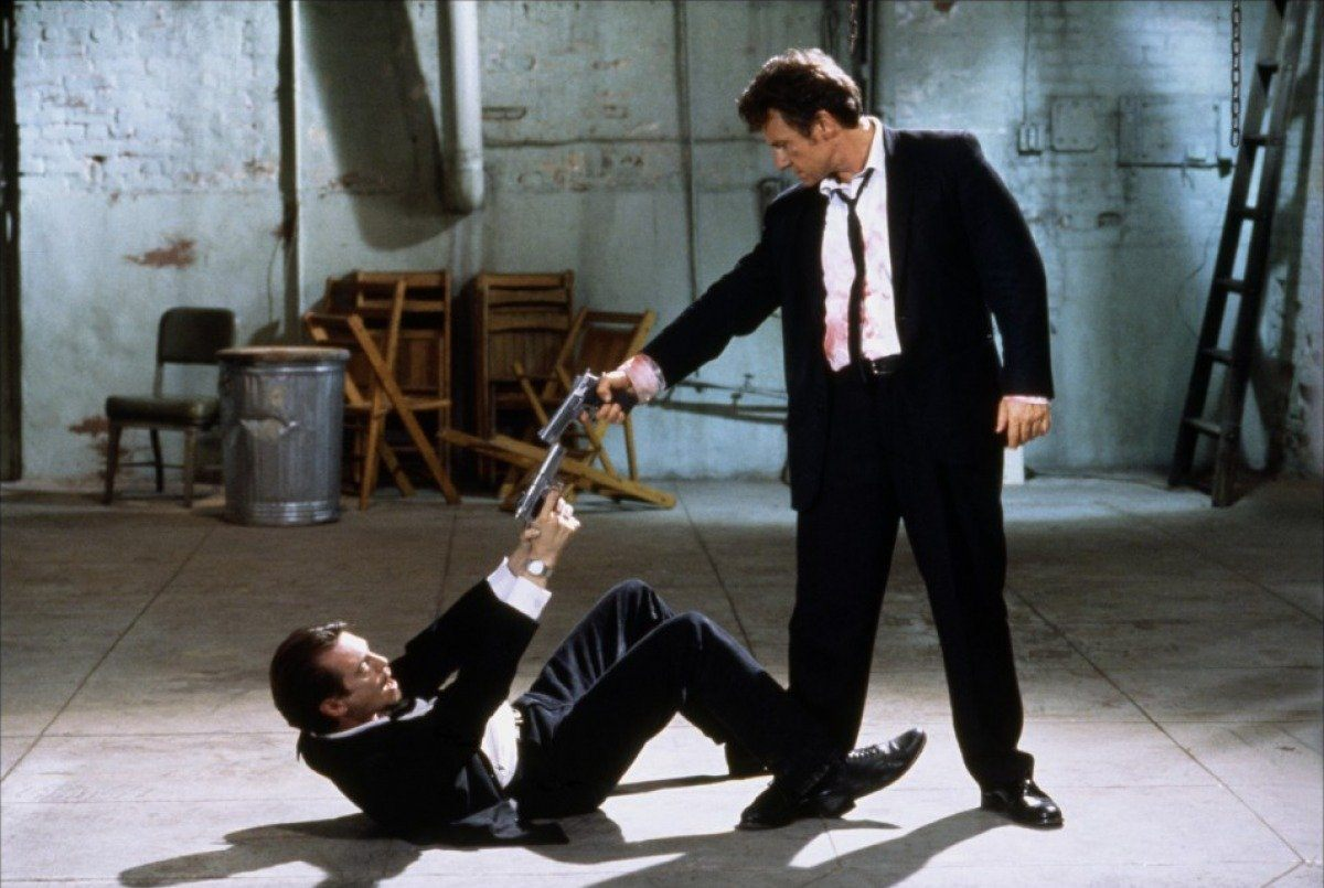 Mr. White standing over Mr. Pink who is lying on the ground, and the two are pointing guns at each other