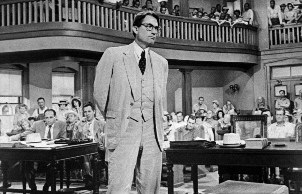 Atticus Finch stands in a court room in black-and-white