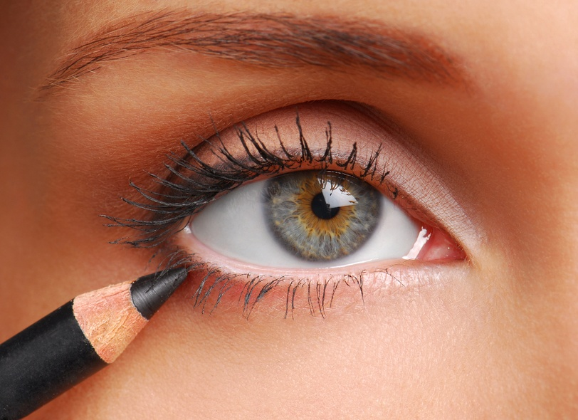 woman applying black eyeliner