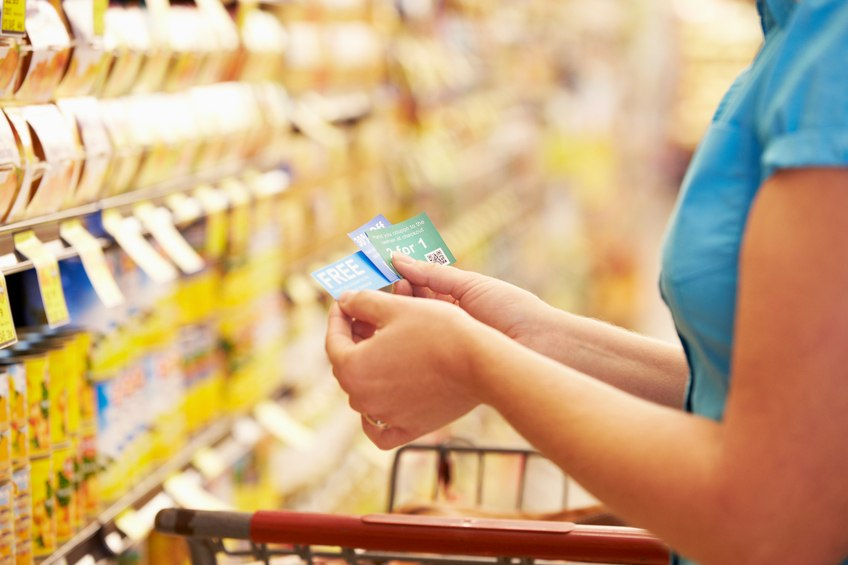 A woman looks at coupons in a grocery aisle of a supermarket