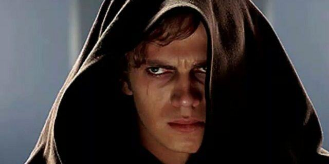 Actor Hayden Christensen looking glum in a hooded cloak as Anakin.