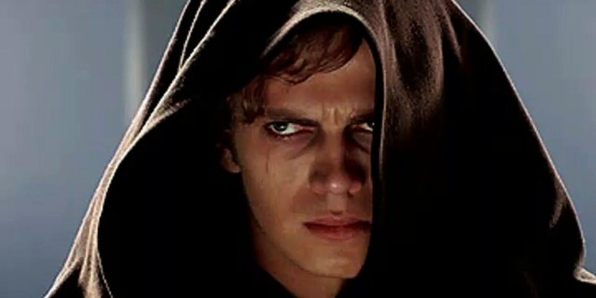 Actor Hayden Christensen looking glum in a hooded cloak as Anakin