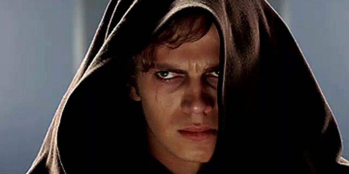 Actor Hayden Christensen looking glum in a hooded cloak as Anakin.