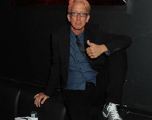 Andy Dick is sitting on a couch and giving a thumbs up.