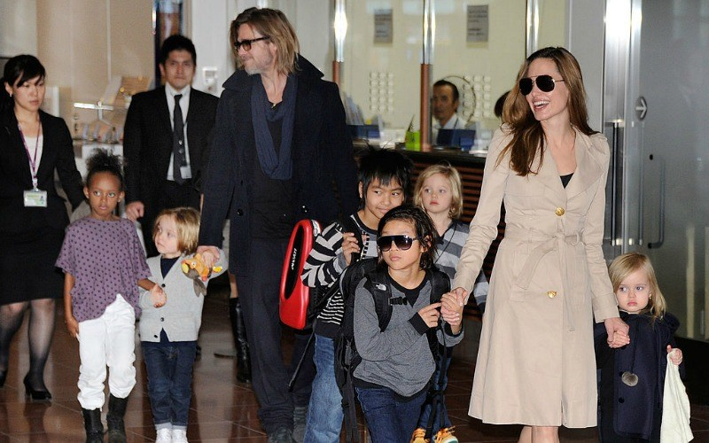 Brad Pitt and Angelina Jolie walk with their kids through an airport