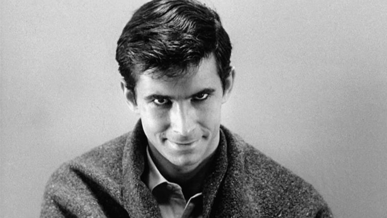 Anthony Perkins as Norman Bates in Psycho is smirking at the camera.
