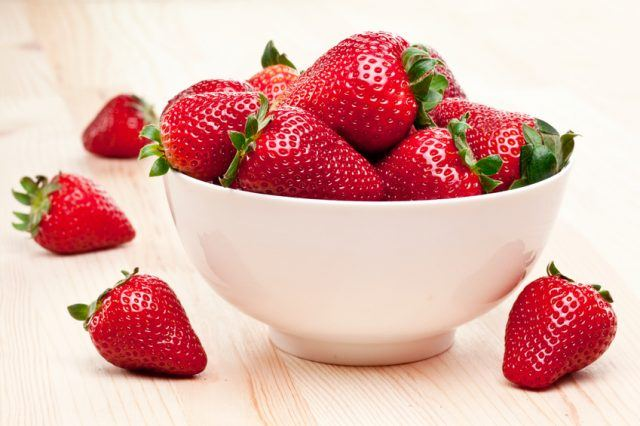 Fresh strawberries in a white bowl.