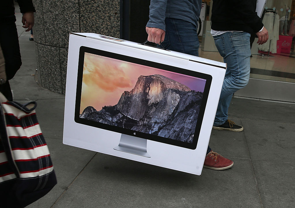 Apple Store customer carries a brand new iMac computer