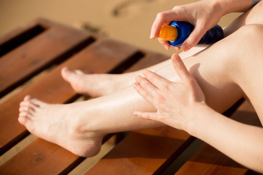 Young woman applying sunblock cream on legs