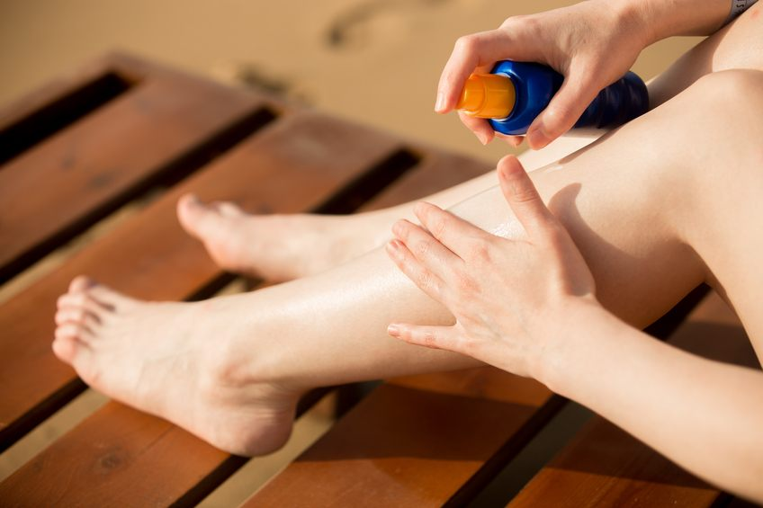Young woman applying sunblock cream on legs