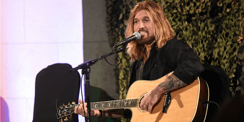 Billy Ray Cyrus holds a guitar