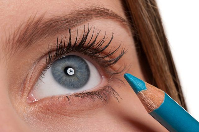 Close-up of a blue eye with a blue eyeliner pencil