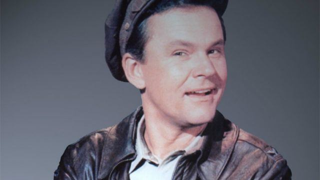 Bob Crane in 'Hogan's Heroes' smiling in front of a gray background.