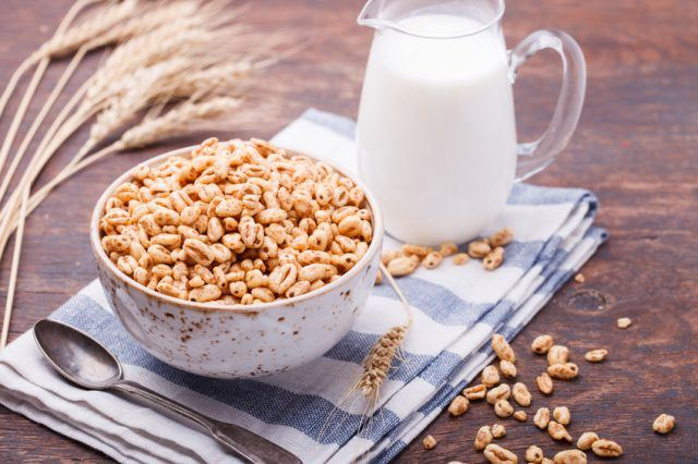 Puffed rice and a jug of milk on a table.