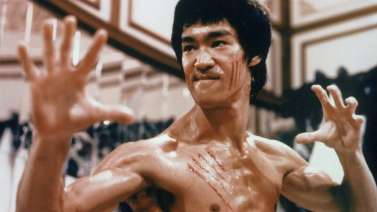 Bruce Lee with his hands out, shirtless, and ready to fight