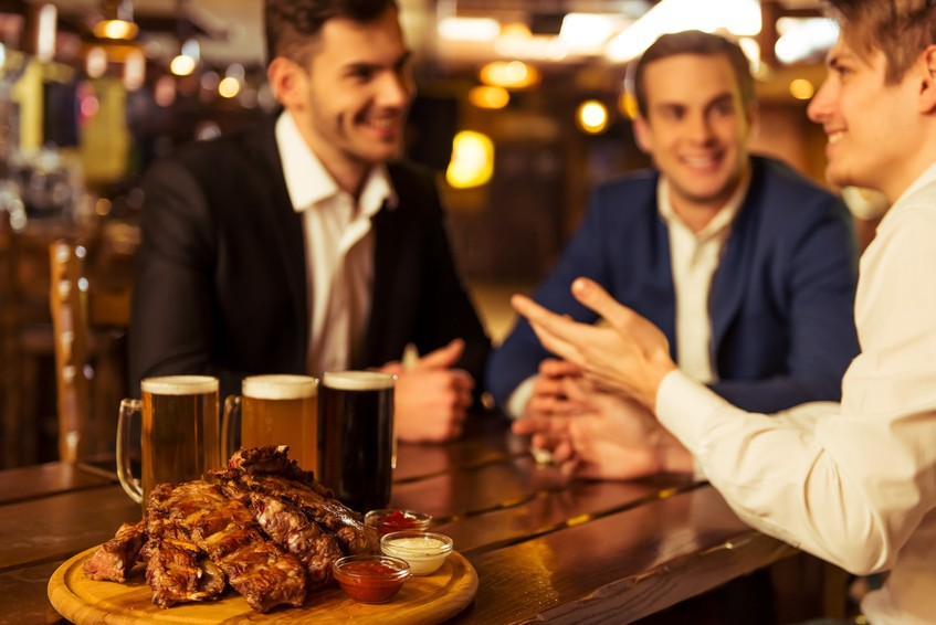 Three young businessmen in suits are smiling, talking and drinking beer