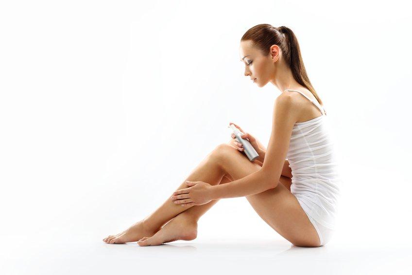 woman rubbing into the leg skin