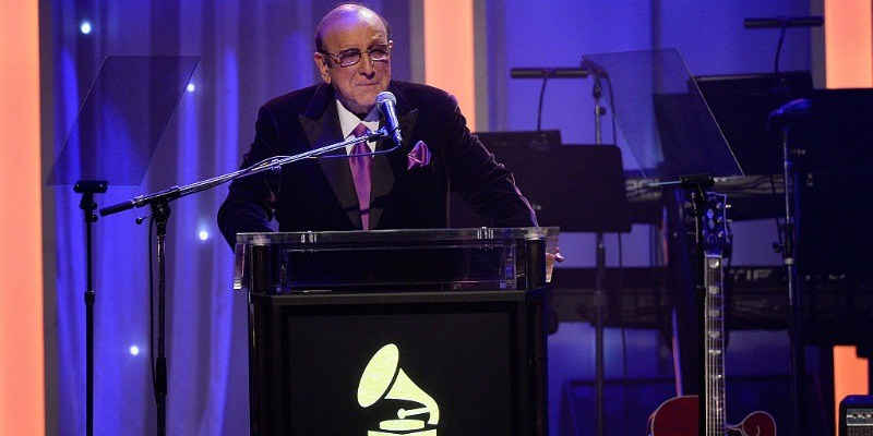 Clive Davis standing at a podium in a suit, getting ready to speak