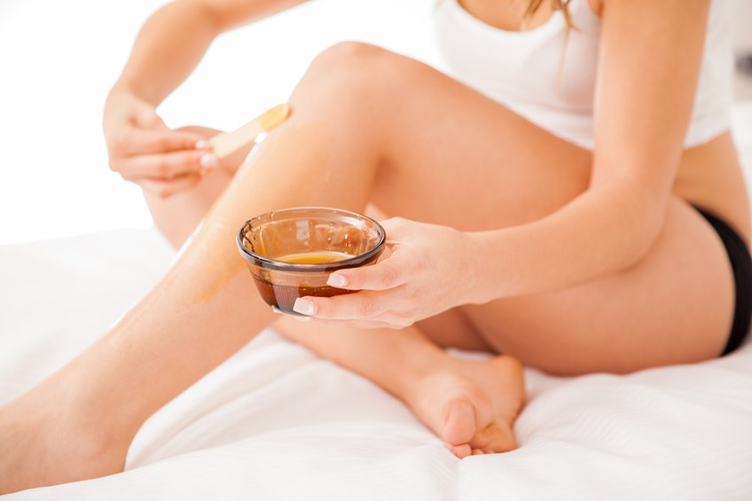 woman putting some wax on legs