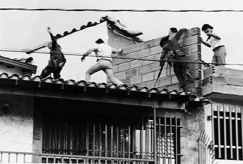 Colombian police and military forces storm the rooftop where drug lord Pablo Escobar was shot dead just moments earlier | JESUS ABAD-EL COLOMBIANO/Getty Images