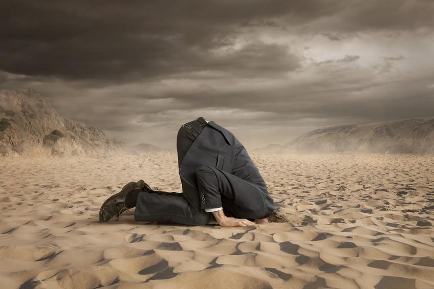 businessman hiding head in the sand