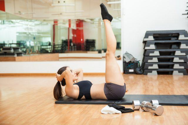 A woman does an ab workout in a studio section of a gym.
