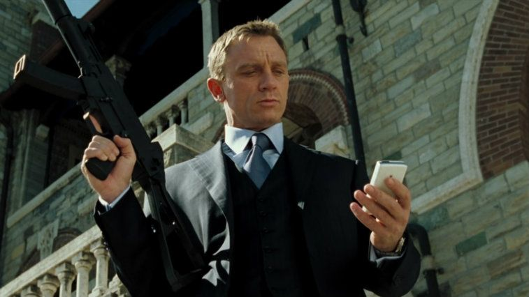 Daniel Craig holds up a gun and looks at his phone in Casino Royale