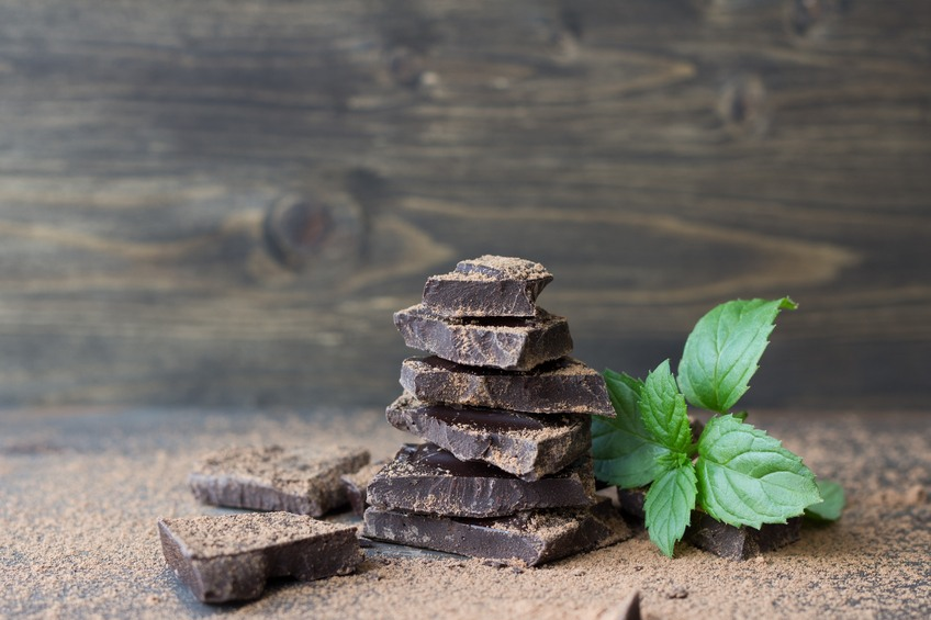 Dark chocolate with mint sprinkled with cocoa powder on a wooden surface