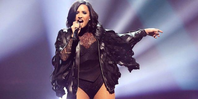 Demi Lovato sings on stage holding a microphone and wearing a leather jacket.