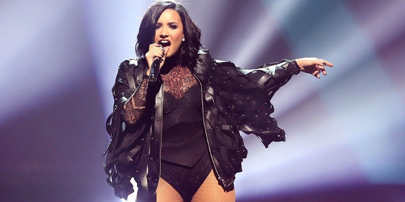 Demi Lovato is singing in a black body suit and leather jacket on stage.